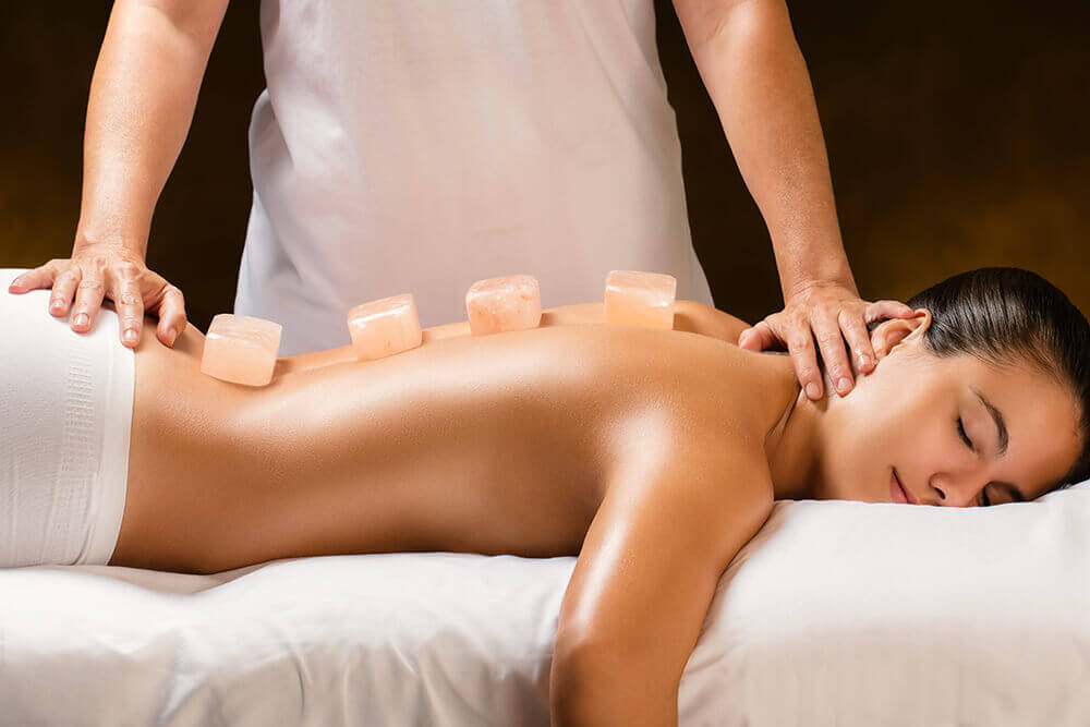 Woman laying on spa bed having a Himalayan salt stone massage