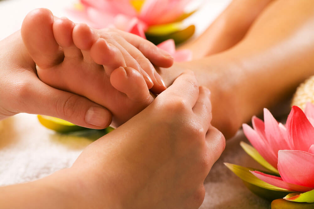 Hands performing foot reflexology