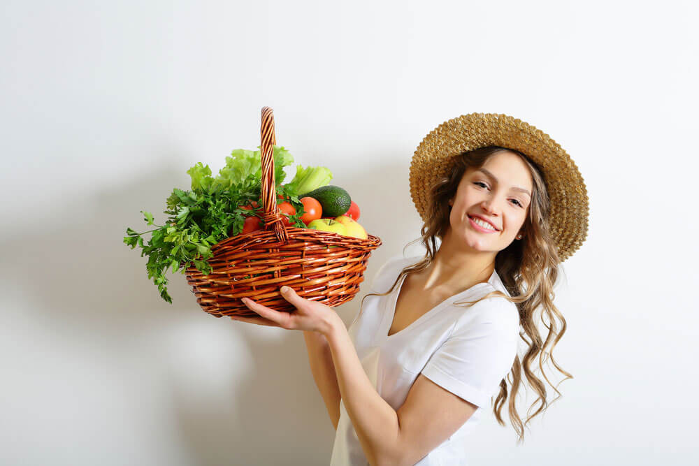 Woman holding large basket of colorful vegetables