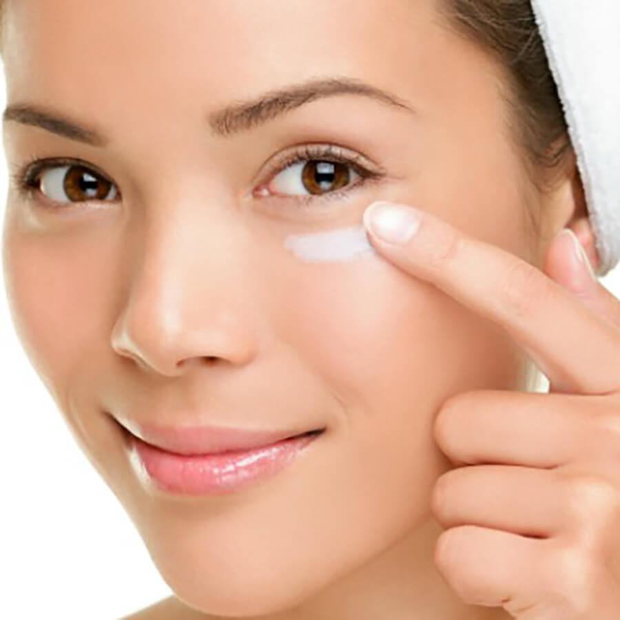 Woman applying eye cream serum to her face