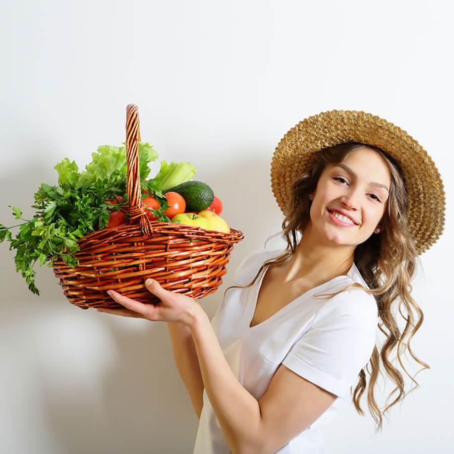 Vegan woman holding a basket of vegetables