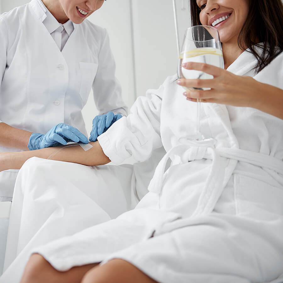 Woman receiving an IV treatment while holding a glass of water