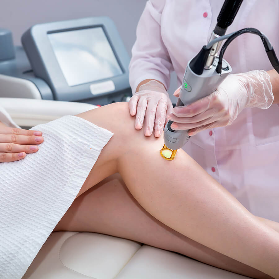 Woman getting hair removal and laser treatment on her leg