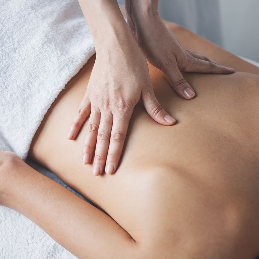 Two hands giving someone a deep tissue massage on her back