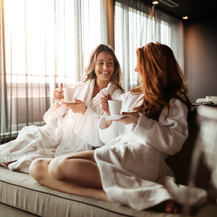 Two young women in robes drinking tea ahead of going into a sauna version two