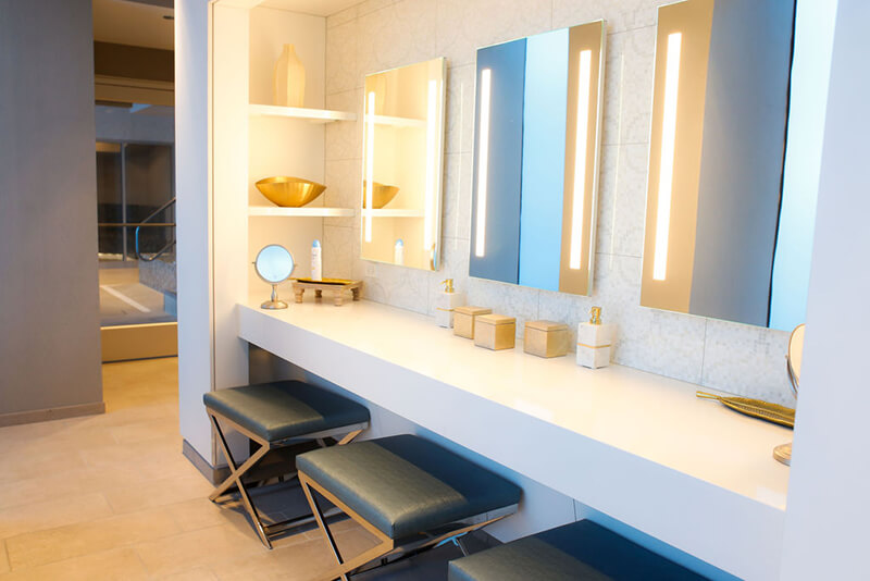Emerge River Spirit mirrors on wall with stools in front of counter