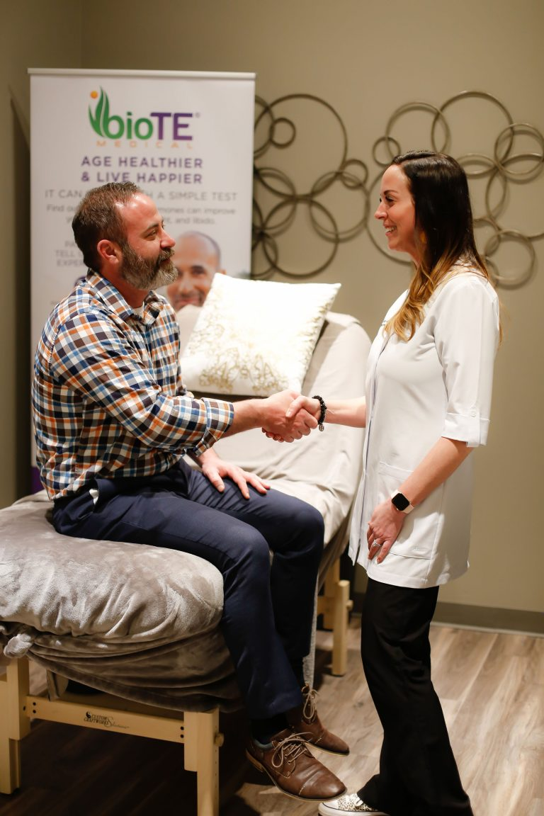 Female consultant shaking hands with a male customer in a treatment room
