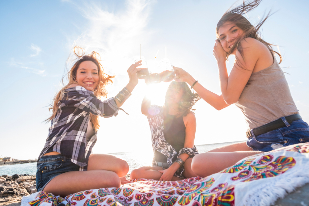 Three young women on a beach in the sun