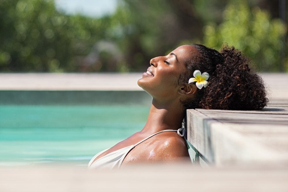 Young woman with flower in her hair relaxing in a pool