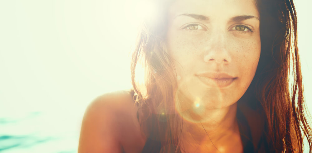 Beautiful brunette in the sun smiling on beach