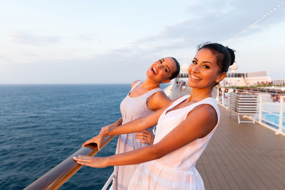 happy young women on cruise deck enjoying themselves, brown hair